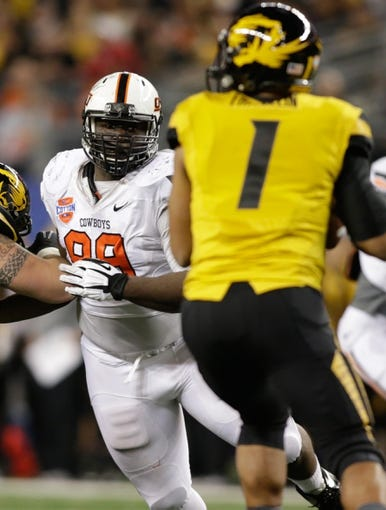 Jan 3, 2014; Arlington, TX, USA; Oklahoma State Cowboys defensive tackle Calvin Barnett (99) rushes Missouri Tigers quarterback James Franklin (1) in the game at the 2014 Cotton Bowl at AT&T Stadium. Missouri beat Oklahoma State 41-31. Mandatory Credit: Tim Heitman-USA TODAY Sports