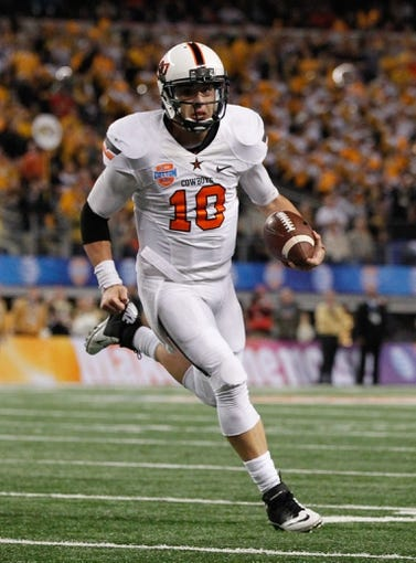 Jan 3, 2014; Arlington, TX, USA; Oklahoma State Cowboys quarterback Clint Chelf (10) runs with the ball in the game against the Missouri Tigers at the 2014 Cotton Bowl at AT&T Stadium. Missouri beat Oklahoma State 41-31. Mandatory Credit: Tim Heitman-USA TODAY Sports