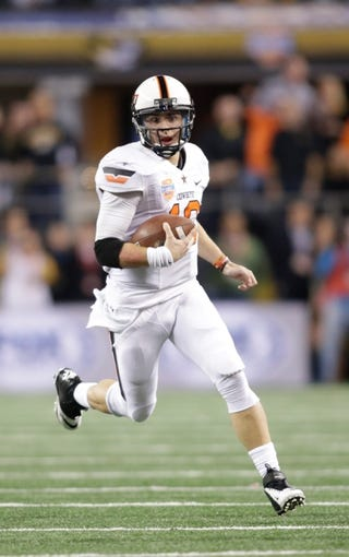 Jan 3, 2014; Arlington, TX, USA; Oklahoma State Cowboys quarterback Clint Chelf (10) runs the ball in the game against the Missouri Tigers at the 2014 Cotton Bowl at AT&T Stadium. Missouri beat Oklahoma State 41-31. Mandatory Credit: Tim Heitman-USA TODAY Sports