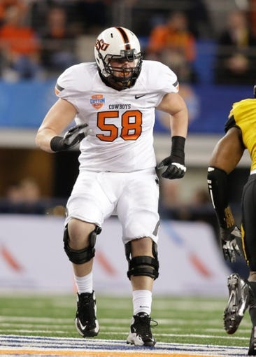 Jan 3, 2014; Arlington, TX, USA; Oklahoma State Cowboys offensive linesman Daniel Koenig (58) in game action against the Missouri Tigers at the 2014 Cotton Bowl at AT&T Stadium. Missouri beat Oklahoma State 41-31. Mandatory Credit: Tim Heitman-USA TODAY Sports