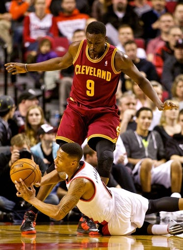 Jan 15, 2014; Portland, OR, USA; Portland Trail Blazers point guard Damian Lillard (0) passes the ball as he falls in front of Cleveland Cavaliers small forward Luol Deng (9) at the Moda Center. Mandatory Credit: Craig Mitchelldyer-USA TODAY Sports