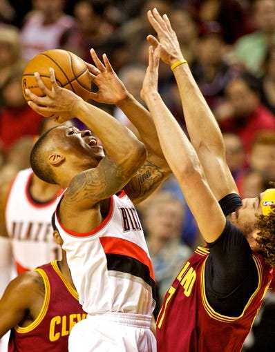 Jan 15, 2014; Portland, OR, USA; Portland Trail Blazers point guard Damian Lillard (0) shoots the ball over Cleveland Cavaliers center Anderson Varejao (17) at the Moda Center. Mandatory Credit: Craig Mitchelldyer-USA TODAY Sports