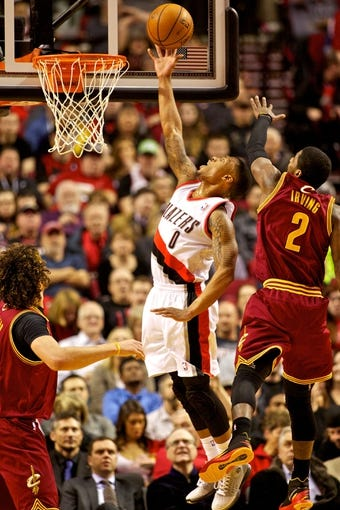 Jan 15, 2014; Portland, OR, USA; Portland Trail Blazers point guard Damian Lillard (0) shoots the ball over Cleveland Cavaliers point guard Kyrie Irving (2) at the Moda Center. Mandatory Credit: Craig Mitchelldyer-USA TODAY Sports