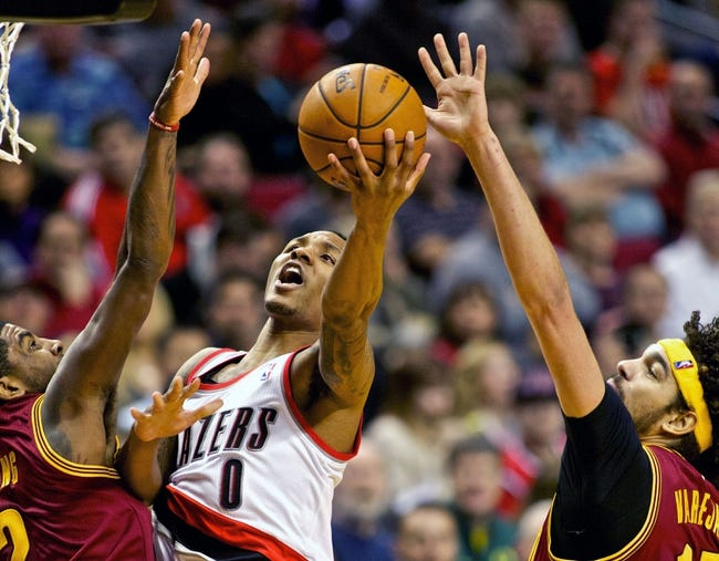 Jan 15, 2014; Portland, OR, USA; Portland Trail Blazers point guard Damian Lillard (0) shoots over Cleveland Cavaliers point guard Kyrie Irving (2) at the Moda Center. Mandatory Credit: Craig Mitchelldyer-USA TODAY Sports