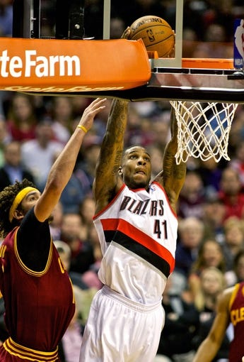 Jan 15, 2014; Portland, OR, USA; Portland Trail Blazers power forward Thomas Robinson (41) dunks over Cleveland Cavaliers center Anderson Varejao (17) at the Moda Center. Mandatory Credit: Craig Mitchelldyer-USA TODAY Sports