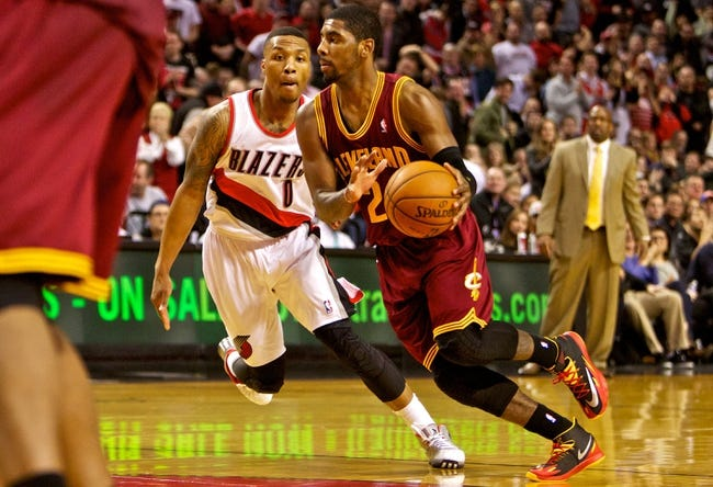 Jan 15, 2014; Portland, OR, USA; Cleveland Cavaliers point guard Kyrie Irving (2) dribbles the ball past Portland Trail Blazers point guard Damian Lillard (0) in the fourth quarter at the Moda Center. Mandatory Credit: Craig Mitchelldyer-USA TODAY Sports