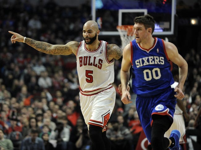 Jan 18, 2014; Chicago, IL, USA;  Chicago Bulls power forward Carlos Boozer (5) points after making a shot as Philadelphia 76ers center Spencer Hawes (00) is nearby during the first quarter at the United Center. Mandatory Credit: David Banks-USA TODAY Sports