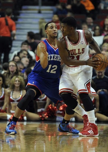 Jan 18, 2014; Chicago, IL, USA; Philadelphia 76ers small forward Evan Turner (12) defends Chicago Bulls shooting guard Jimmy Butler (21) during the first quarter at the United Center. Mandatory Credit: David Banks-USA TODAY Sports