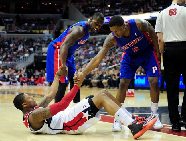 Jan 18, 2014; Washington, DC, USA; Washington Wizards guard Bradley Beal (3) is helped off the floor by Detroit Pistons guard Kentavious Caldwell-Pope (5) and guard Rodney Stuckey (3) at Verizon Center. Mandatory Credit: Evan Habeeb-USA TODAY Sports