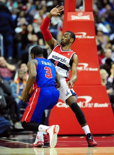 Jan 18, 2014; Washington, DC, USA; Detroit Pistons guard Rodney Stuckey (3) is called for an offensive foul against Washington Wizards guard John Wall (2) at Verizon Center. Mandatory Credit: Evan Habeeb-USA TODAY Sports