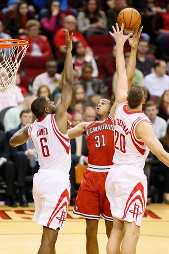Jan 18, 2014; Houston, TX, USA; Milwaukee Bucks center John Henson (31) shoots while being defended by Houston Rockets forward Terrence Jones (6) and Donatas Motiejunas (20) during the second half at Toyota Center. The Rockets won 114-104. Mandatory Credit: Soobum Im-USA TODAY Sports