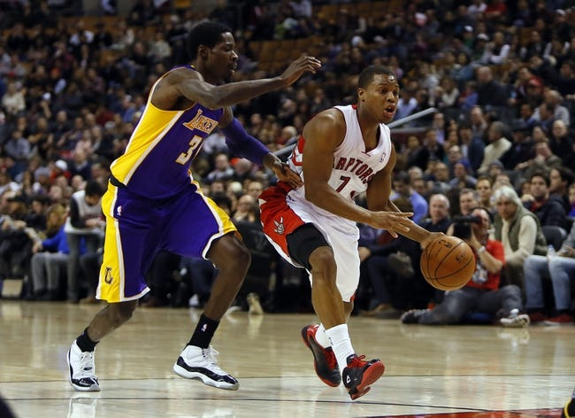 Jan 19, 2014; Toronto, Ontario, CAN; Toronto Raptors guard Kyle Lowry (7) looks to pass as Los Angeles Lakers guard Manny Harris (3) defends during the first half at the Air Canada Centre. Mandatory Credit: John E. Sokolowski-USA TODAY Sports