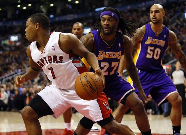 Jan 19, 2014; Toronto, Ontario, CAN; Toronto Raptors guard Kyle Lowry (7) controls the ball against Los Angeles Lakers forward-center Jordan Hill (27) and center Robert Sacre (50) during the first half at the Air Canada Centre. Mandatory Credit: John E. Sokolowski-USA TODAY Sports