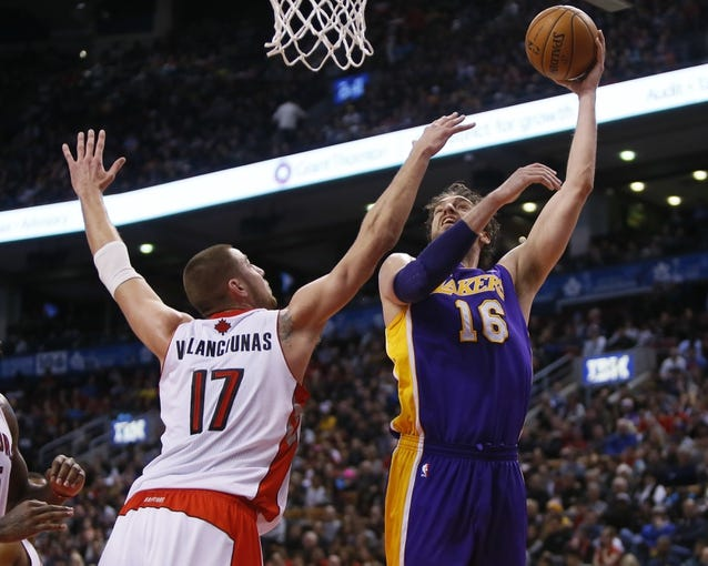 Jan 19, 2014; Toronto, Ontario, CAN; Los Angeles Lakers center-forward Pau Gasol (16) goes to make a basket as Toronto Raptors center Jonas Valanciunas (17) defends at the Air Canada Centre. Los Angeles defeated Toronto 112-106. Mandatory Credit: John E. Sokolowski-USA TODAY Sports