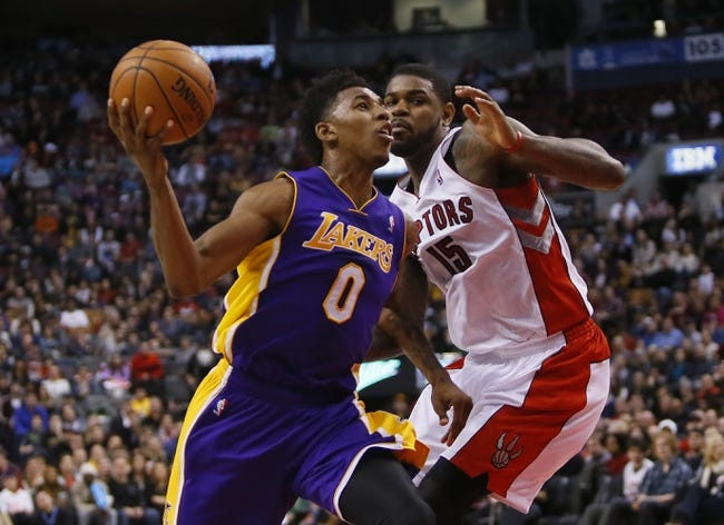 Jan 19, 2014; Toronto, Ontario, CAN; Los Angeles Lakers forward-guard Nick Young (0) gets by Toronto Raptors forward-center Amir Johnson (15) at the Air Canada Centre. Los Angeles defeated Toronto 112-106. Mandatory Credit: John E. Sokolowski-USA TODAY Sports