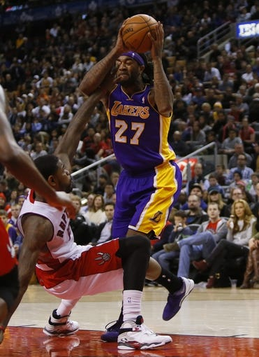 Jan 19, 2014; Toronto, Ontario, CAN; Los Angeles Lakers forward-center Jordan Hill (27) tries to get off a pass as Toronto Raptors forward-center Amir Johnson (15) defends at the Air Canada Centre. Los Angeles defeated Toronto 112-106. Mandatory Credit: John E. Sokolowski-USA TODAY Sports