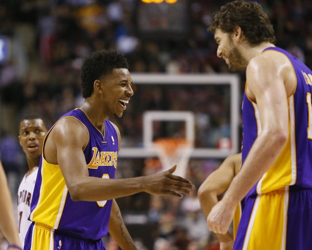 Jan 19, 2014; Toronto, Ontario, CAN; Los Angeles Lakers center-forward Pau Gasol (right) congratulates forward-guard Nick Young (0) looks on at the Air Canada Centre. Los Angeles defeated Toronto 112-106. Mandatory Credit: John E. Sokolowski-USA TODAY Sports