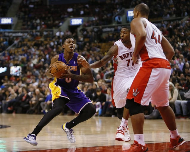 Jan 19, 2014; Toronto, Ontario, CAN; Los Angeles Lakers forward-guard Nick Young (0) goes to shoot as Toronto Raptors guard Julyan Stone (77) and center-forward Chuck Hayes (44) defend at the Air Canada Centre. Los Angeles defeated Toronto 112-106. Mandatory Credit: John E. Sokolowski-USA TODAY Sports