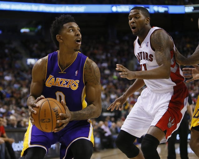Jan 19, 2014; Toronto, Ontario, CAN; Los Angeles Lakers forward-guard Nick Young (0) goes to shoot as Toronto Raptors guard Julyan Stone (77) defends at the Air Canada Centre. Los Angeles defeated Toronto 112-106. Mandatory Credit: John E. Sokolowski-USA TODAY Sports
