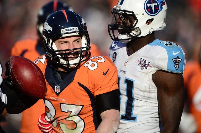 Dec 8, 2013; Denver, CO, USA; Denver Broncos wide receiver Wes Welker (83) catches in front of Tennessee Titans strong safety Bernard Pollard (31) in the second quarter at Sports Authority Field at Mile High. Mandatory Credit: Ron Chenoy-USA TODAY Sports