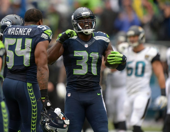 Sep 22, 2013; Seattle, WA, USA; Seattle Seahawks safety Kam Chancellor (31) celebrates with linebacker Bobby Wagner (54) after intercepting a pass in the fourth quarter against the Jacksonville Jaguars at CenturyLink Field. The Seahawks defeated the Jaguars 45-17. Mandatory Credit: Kirby Lee-USA TODAY Sports