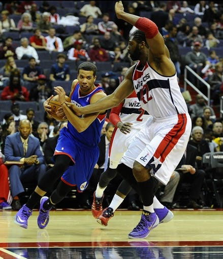 Jan 20, 2014; Washington, DC, USA; Philadelphia 76ers point guard Michael Carter-Williams (1) dribbles as Washington Wizards power forward Nene Hilario (42) defends during the second half at Verizon Center. The Wizards defeated the 76ers 107 - 99. Mandatory Credit: Brad Mills-USA TODAY Sports
