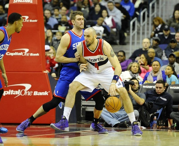 Jan 20, 2014; Washington, DC, USA; Washington Wizards center Marcin Gortat (4) dribbles the ball as Philadelphia 76ers center Spencer Hawes (00) defends during the second half at Verizon Center. The Wizards defeated the 76ers 107 - 99. Mandatory Credit: Brad Mills-USA TODAY Sports