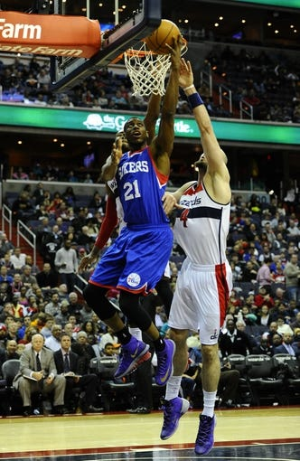 Jan 20, 2014; Washington, DC, USA; Philadelphia 76ers power forward Thaddeus Young (21) shoots as Washington Wizards point guard John Wall (2) defends during the second half at Verizon Center. The Wizards defeated the 76ers 107 - 99. Mandatory Credit: Brad Mills-USA TODAY Sports