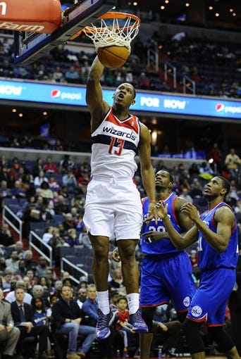 Jan 20, 2014; Washington, DC, USA; Washington Wizards center Kevin Seraphin (13) dunks the ball as Philadelphia 76ers power forward Thaddeus Young (21) looks on during the first half at Verizon Center. Mandatory Credit: Brad Mills-USA TODAY Sports