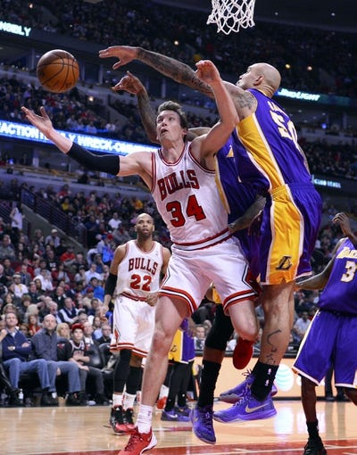 Jan 20, 2014; Chicago, IL, USA; Chicago Bulls small forward Mike Dunleavy (34) is fouled by Los Angeles Lakers center Robert Sacre (50) during the second half at United Center. The Bulls defeat the Lakers 102-100 in overtime. Mandatory Credit: Mike DiNovo-USA TODAY Sports