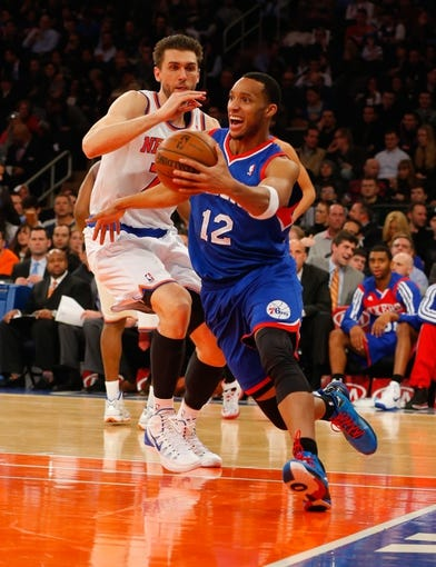 Jan 22, 2014; New York, NY, USA;  Philadelphia 76ers small forward Evan Turner (12) drives to the basket during the first half against New York Knicks center Andrea Bargnani (77) at Madison Square Garden. Mandatory Credit: Jim O'Connor-USA TODAY Sports