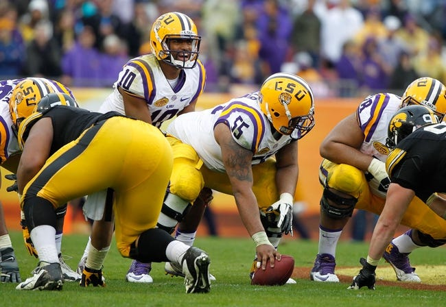 Jan 1, 2014; Tampa, Fl, USA; LSU Tigers quarterback Anthony Jennings (10) calls a play as LSU Tigers center Elliott Porter (55) hikes the ball against the Iowa Hawkeyes  during the first half at Raymond James Stadium. Mandatory Credit: Kim Klement-USA TODAY Sports