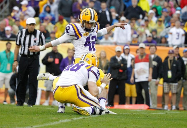 Jan 1, 2014; Tampa, Fl, USA; LSU Tigers kicker Colby Delahoussaye (42) kicks as linebacker Seth Fruge (48) hold the ball against the Iowa Hawkeyes during the first half at Raymond James Stadium. Mandatory Credit: Kim Klement-USA TODAY Sports