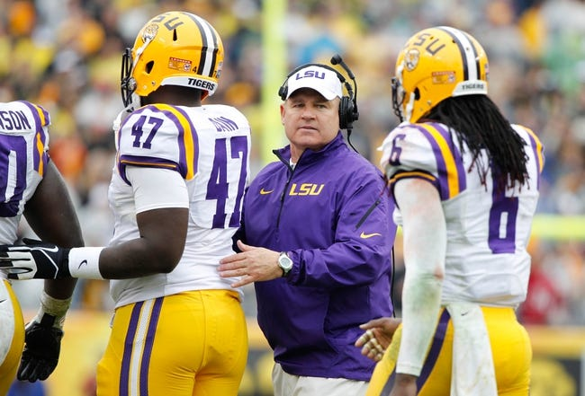 Jan 1, 2014; Tampa, Fl, USA; LSU Tigers head coach Les Miles congratulates defensive tackle Maquedius Bain (47) and safety Craig Loston (6) during the second half against the Iowa Hawkeyes at Raymond James Stadium. LSU Tigers defeated the Iowa Hawkeyes 21-14. Mandatory Credit: Kim Klement-USA TODAY Sports