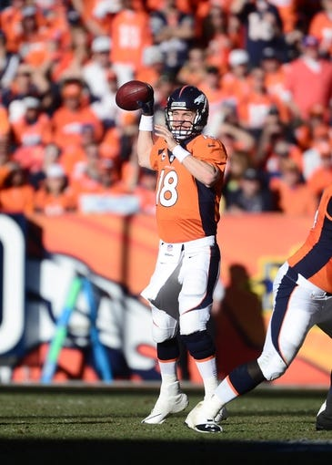 January 19, 2014; Denver, CO, USA; Denver Broncos quarterback Peyton Manning (18) throws against the New England Patriots in the first half of the 2013 AFC Championship football game at Sports Authority Field at Mile High. Mandatory Credit: Ron Chenoy-USA TODAY Sports