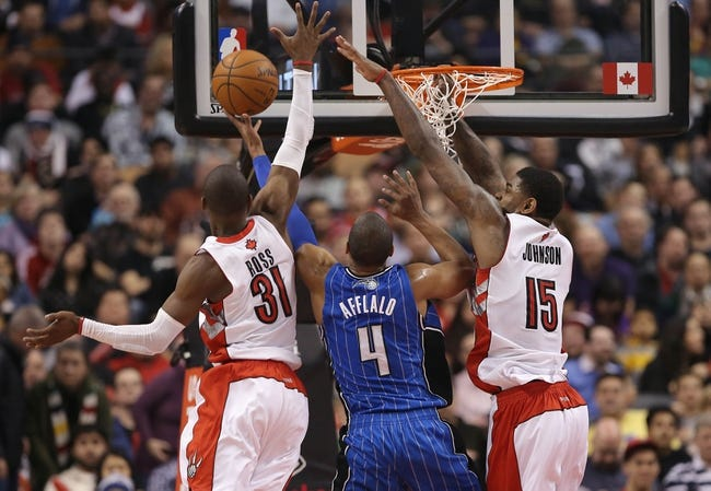 Jan 29, 2014; Toronto, Ontario, CAN; Orlando Magic shooting guard Arron Afflalo (4) is blocked by Toronto Raptors guard Terrence Ross (31) as he goes to the basket at Air Canada Centre. The Raptors beat the Magic 98-83. Mandatory Credit: Tom Szczerbowski-USA TODAY Sports