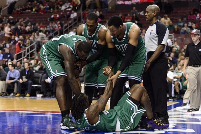 Feb 5, 2014; Philadelphia, PA, USA; Boston Celtics forward Brandon Bass (30) guard Rajon Rondo (9) and center Jared Sullinger (7) help forward Gerald Wallace (45) up off the floor during the fourth quarter against the Philadelphia 76ers at the Wells Fargo Center. The Celtics defeated the Sixers 114-108. Mandatory Credit: Howard Smith-USA TODAY Sports