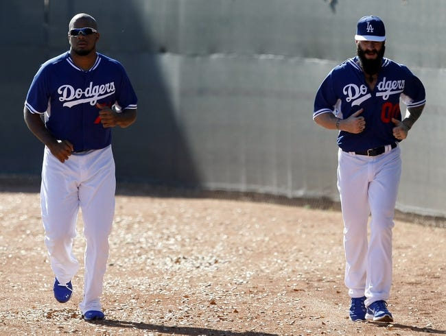Feb 9, 2014; Glendale, AZ, USA; Los Angeles Dodgers relief pitcher Kenley Jansen (74) and Brian Wilson (00) run the field during the first day of camp at Camelback Ranch. Mandatory Credit: Rick Scuteri-USA TODAY Sports