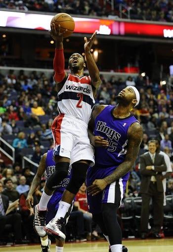 Feb 9, 2014; Washington, DC, USA; Washington Wizards point guard John Wall (2) shoots a layup as Sacramento Kings center DeMarcus Cousins (15) defends during the first half at Verizon Center. Mandatory Credit: Brad Mills-USA TODAY Sports