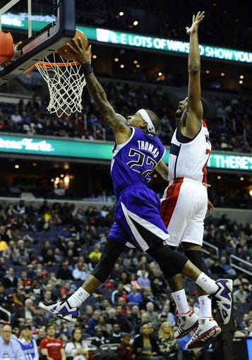 Feb 9, 2014; Washington, DC, USA; Sacramento Kings point guard Isaiah Thomas (22) shoots as Washington Wizards point guard John Wall (2) defends during the second half at Verizon Center. The Wizards defeated the Kings 93 - 84. Mandatory Credit: Brad Mills-USA TODAY Sports