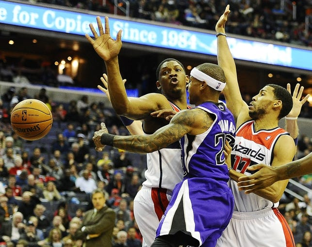 Feb 9, 2014; Washington, DC, USA; Sacramento Kings point guard Isaiah Thomas (22) passes the ball as Washington Wizards center Kevin Seraphin (13) and Washington Wizards shooting guard Garrett Temple (17) defend during the second half at Verizon Center. The Wizards defeated the Kings 93 - 84. Mandatory Credit: Brad Mills-USA TODAY Sports