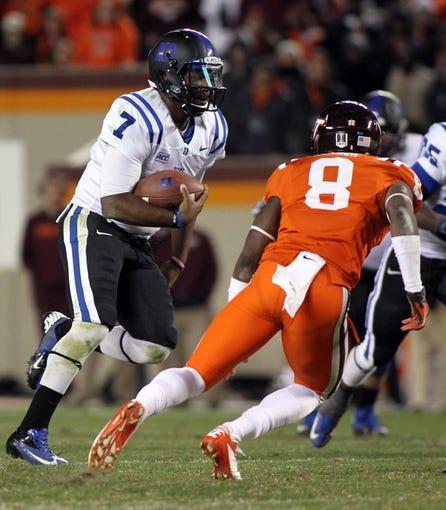 Oct 26, 2013; Blacksburg, VA, USA; Duke Blue Devils quarterback Anthony Boone (7) runs the ball against Virginia Tech Hokies safety Detrick Bonner (8) at Lane Stadium. Mandatory Credit: Peter Casey-USA TODAY Sports