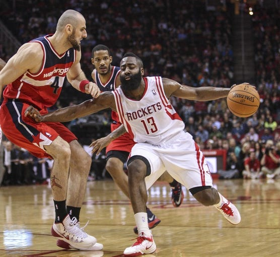Feb 12, 2014; Houston, TX, USA; Houston Rockets shooting guard James Harden (13) drives the ball during the second quarter as Washington Wizards center Marcin Gortat (4) defends at Toyota Center. Mandatory Credit: Troy Taormina-USA TODAY Sports