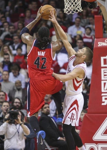Feb 12, 2014; Houston, TX, USA; Washington Wizards power forward Nene Hilario (42) drives to the basket during the second quarter as Houston Rockets small forward Chandler Parsons (25) defends at Toyota Center. Mandatory Credit: Troy Taormina-USA TODAY Sports