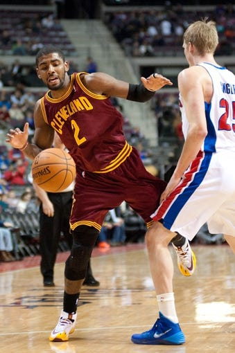 Feb 12, 2014; Auburn Hills, MI, USA; Detroit Pistons small forward Kyle Singler (25) fouls Cleveland Cavaliers point guard Kyrie Irving (2) during the third quarter at The Palace of Auburn Hills. Cleveland won 93-89. Mandatory Credit: Tim Fuller-USA TODAY Sports