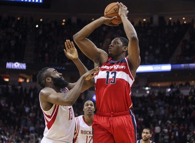 Feb 12, 2014; Houston, TX, USA; Washington Wizards center Kevin Seraphin (13) attempts a shot during the fourth quarter as Houston Rockets shooting guard James Harden (13) defends at Toyota Center. The Rockets defeated the Wizards 113-112. Mandatory Credit: Troy Taormina-USA TODAY Sports
