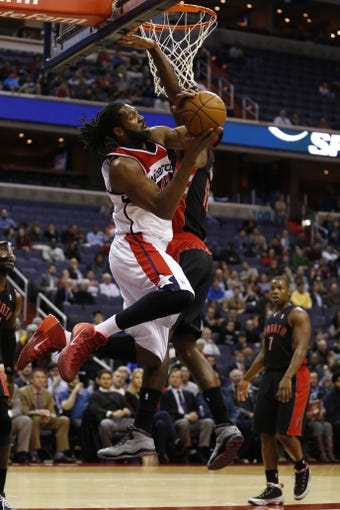 Feb 18, 2014; Washington, DC, USA; Washington Wizards power forward Nene (42) shoots the ball as Toronto Raptors power forward Amir Johnson (15) defends in the first quarter at Verizon Center. Mandatory Credit: Geoff Burke-USA TODAY Sports