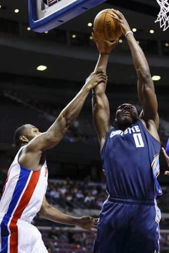 Feb 18, 2014; Auburn Hills, MI, USA; Charlotte Bobcats center Bismack Biyombo (0) is fouled by Detroit Pistons point guard Brandon Jennings (7) in the second quarter at The Palace of Auburn Hills. Mandatory Credit: Rick Osentoski-USA TODAY Sports