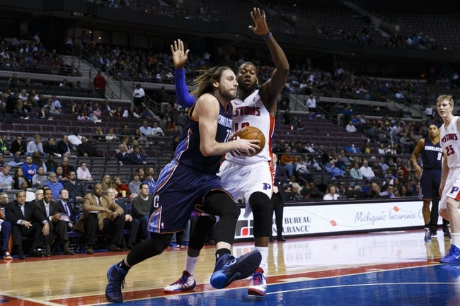 Feb 18, 2014; Auburn Hills, MI, USA; Charlotte Bobcats power forward Josh McRoberts (11) moves the ball defended by Detroit Pistons power forward Greg Monroe (10) in the first quarter at The Palace of Auburn Hills. Mandatory Credit: Rick Osentoski-USA TODAY Sports