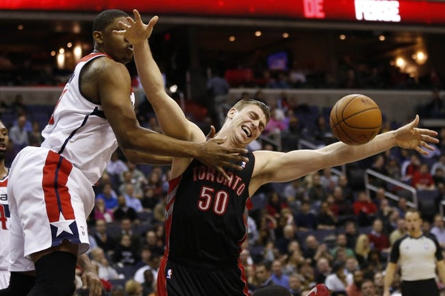 Feb 18, 2014; Washington, DC, USA; Toronto Raptors power forward Tyler Hansbrough (50) loses control of the ball as Washington Wizards center Kevin Seraphin (13) defends in the fourth quarter at Verizon Center. The Raptors won 103-93. Mandatory Credit: Geoff Burke-USA TODAY Sports